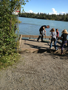 She got to see a Middle Schooler girl land a salmon caught in the Kenai River.  Here the dad is holding up the fish.  Quite exciting.