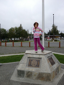 Posing on the new flag pole base at the Soldotna Creek Park and wanting grandmother to take her picture.