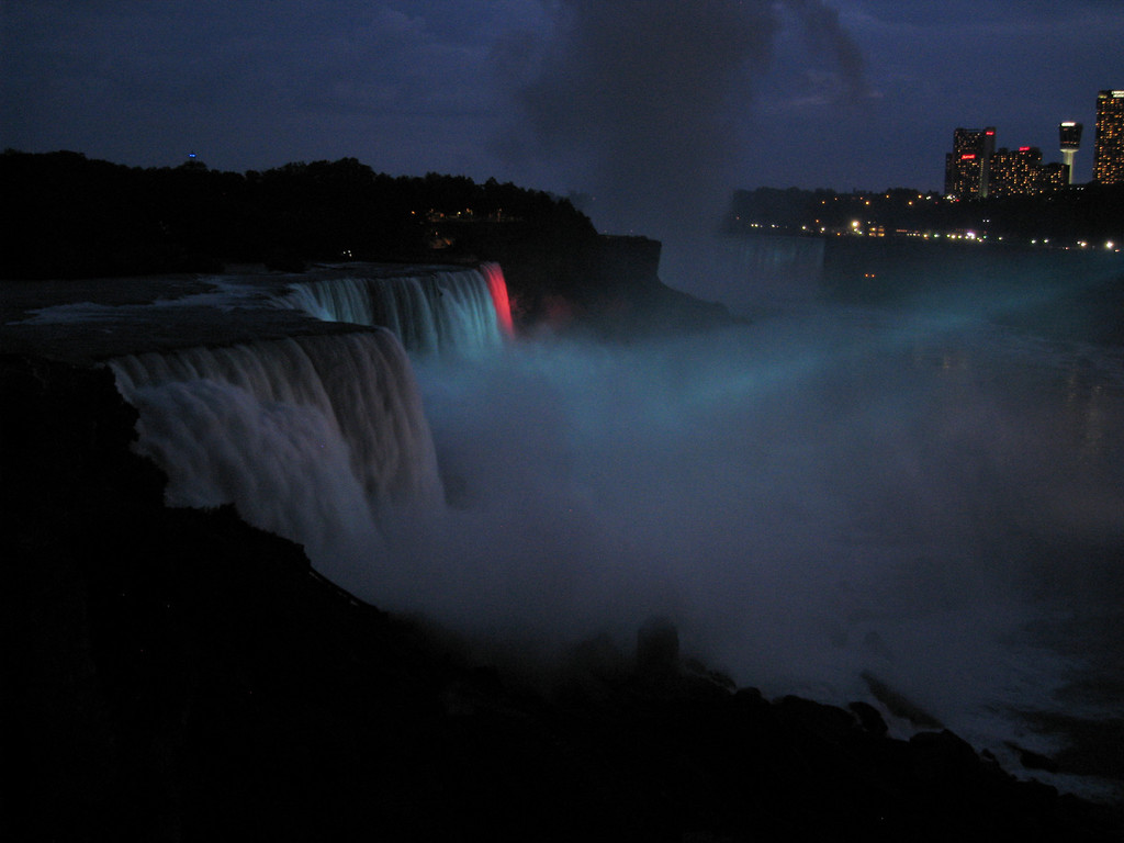 The American and Horseshoe falls are lit by colored spotlights from the Canadian side.