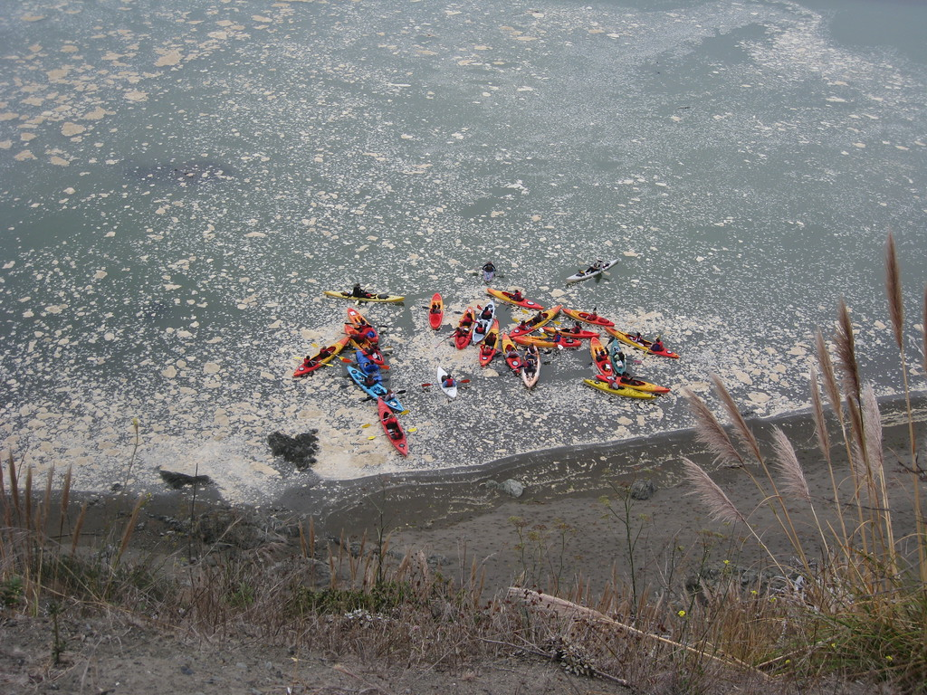 Kayakers at the base of a cliff by the ocean, at the mouth of the Russian River.