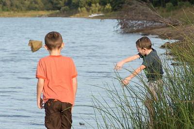 Boys Throwing Rocks Into the Lake