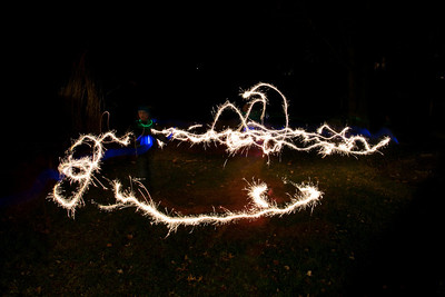 Kids run with sparklers.