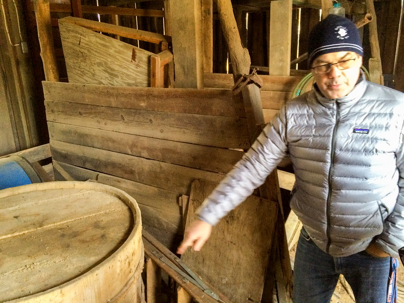 Pete examines a wooden barrel in the original stalls of the barn.