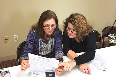 Jillian and Debbie look over the Aloha to Aging newsletter.