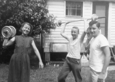 DPB-90: Anne Patterson (nee McKeown) with her sons Billy and Jimmy Patterson in the back yard of 320 West Main Street. The back reads: Walt Thomas got them these weights - but I don't need them