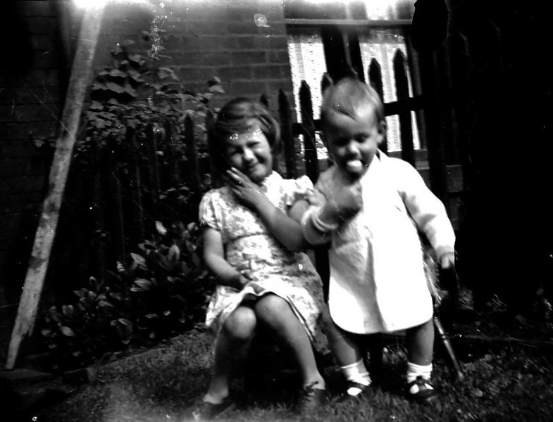 Maureen and Peter Fisher with lolly in yard of 325 abt 1950