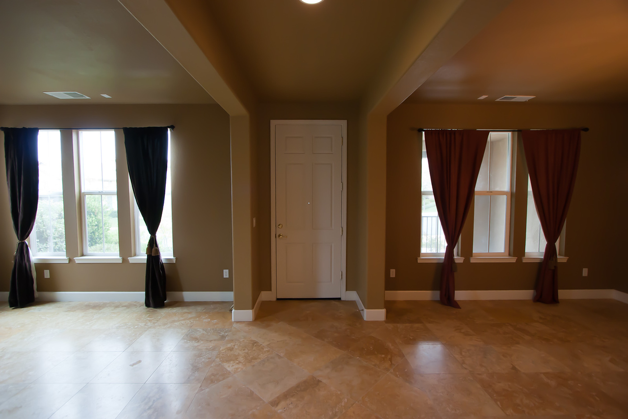 Inside house, behind front door, facing SW.  Tile floor is a natural travertine stone.