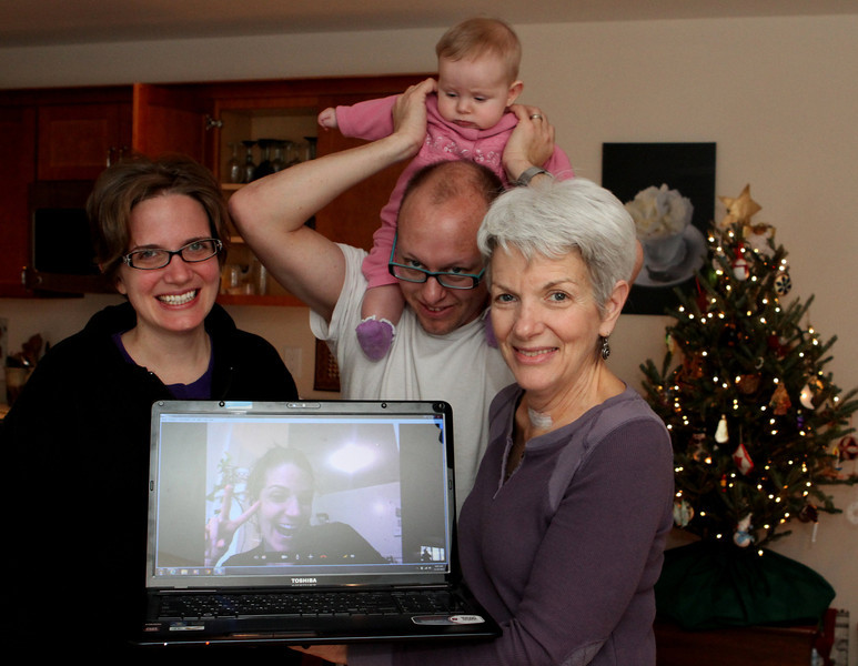 Laura Ann Sweitzer, Oakland, California (via Skype on the laptop screen) sends her greetings and flight info to (L-R) Erica Sweitzer, Mike Sweitzer (Center) with Ruth Grace on his shoulders, and Sarah Sweitzer (far right).  On Christmas Day Laura arrived at Fort Wayne Airport for the Indiana portion of her visit followed by a trip to Middleton, Wisconsin.
