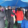 Family gathers under the tent at graveside.