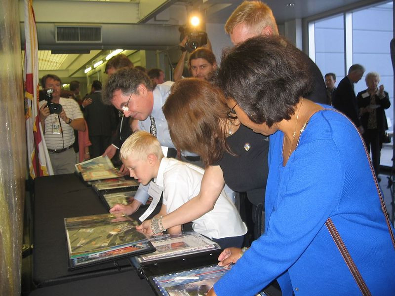 Iain looks at Laurel's scrapbook with Bruce Haviland.