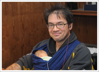 Kento, at work in his home office.  Aiden has to be hooked up to a breathing monitor, because sometimes he forgets to breath.  The monitor has to be carried around when the baby leaves the nursery.