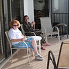 Pat and Kim having coffee in their pajamas on the balcony.
