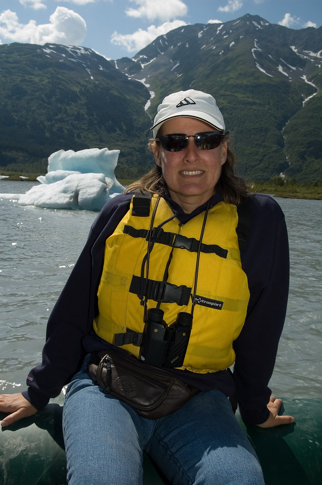 Steph, posing on the raft in front of a distant iceberg.