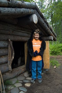 Kevin is wearing a bear skin and standing next to a trapper's house.
