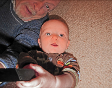 We're lying on the carpet. Zeidi is holding the camera up to take a photo of us, but Karl is pulling on the strap.