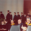 "April 18, 1980<br /> Convocation in JSB auditorium.<br /> Bob approaching the stage where he received his diploma cover (in front of center ""column"").<br /> (note: Marianne & Kelly Hawkes sitting in front row--before we knew them.  Kelly was one of the speakers.)"