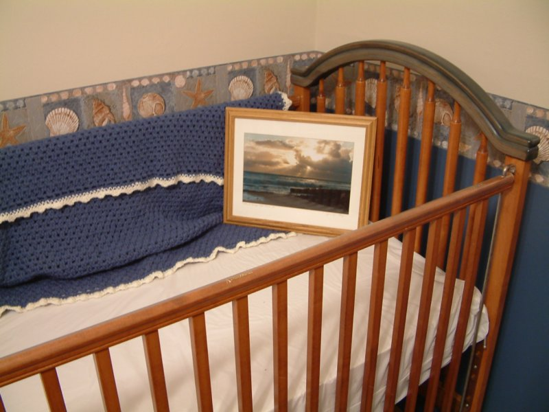 The crib with a handmade blanket from Mrs Savage and a framed picture by Jen Loper which will hang in Alex's bedroom.