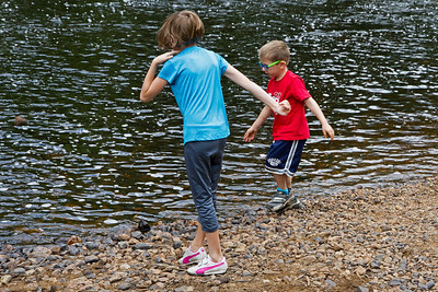 Julianna and Samuel picking and throwing stones into the river