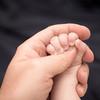 Baby grabbing daddy's thumb. So tiny. But getting bigger!