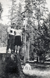 "18. Darrell Levon (""Bunk"") Moore and Marian Johnson/Hosier Moore standing on old-growth stump, c. 1948, Myrtle Creek, OR"