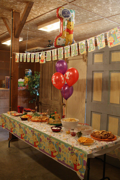 The food table was decorated with a Pooh table cloth, balloons -- including a 1-shaped Pooh balloon -- and a Happy 1st Birthday banner