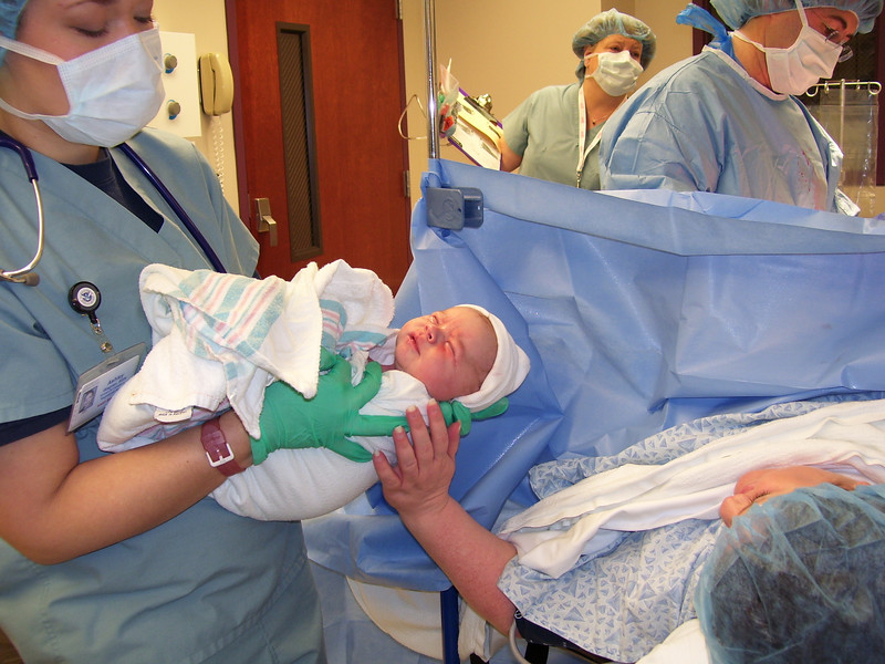"""Oh-wee! His first little hat (one of many he acquired in the hospital; he didn't like them, so they kept """"coming off"""", but everytime he would return from the nursery he had another one to wrestle with), and Mommy's first chance to touch him. How amazing! It would be almost three hours before I would get to see and hold him again."""