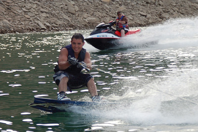 Daniel on wake board while his dad, Miles rides behind