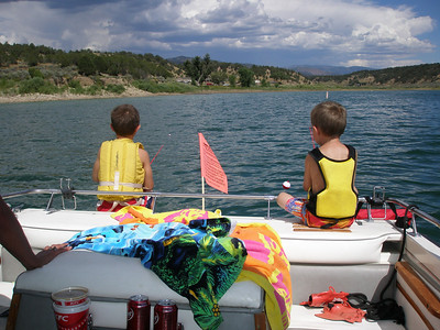 AJ and Jackson fishing off the back of the boat