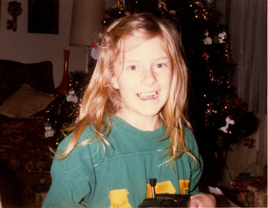"Me at Christmas, probably 1982.  The longest hair I've had ever - still trying to get it back to that length!  I was holding my best present that year - a remote control ""KITT"" car and wearing my brother's frat shirt that I wore until it had holes all over it and the letters fell off!"