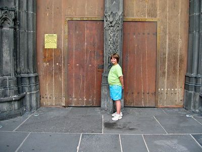 Anna in front of the side door at the Cathedral at center of town.  Name is something Notre Dame. We were able to go inside and look at the artwork and lay a candle for a Saint.