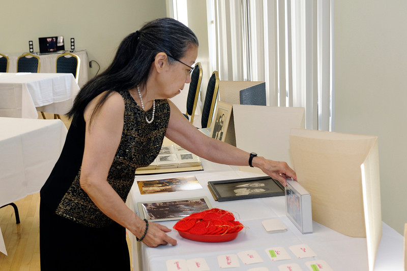Carolyn arranging family photos. She crocheted red hearts for guests of our celebraton.<br /> <br /> (John Hughes-Caley Photo)