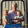 Camden and Claire taking a ride with Papa on the tractor.