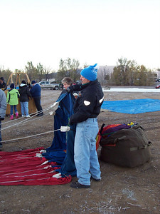 Chris helps prepare to unpack the balloon from the large duffel bag on the ground.