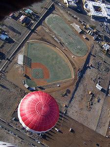 Baseball and soccer fields drifting below.