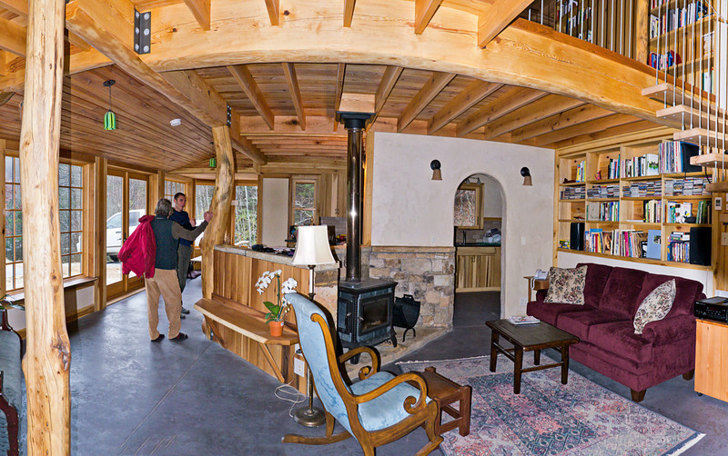 pano of 500 sq ft living/kitchen area from the living side ... some distortion due to pano. Note how the space revolves around the stove, creating sub-spaces. Arch doorway leads into kitchen