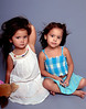 Two little girls sitting together on a grey background and playing model. One girl holding a stuffed toy