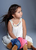 Little girl sitting on a grey background and holding a stuffed toy