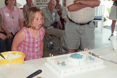 Amanda Snyder takes care of the candles while her grandfather supervises.