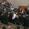 The graduates filed into their seats. John is at end of the row