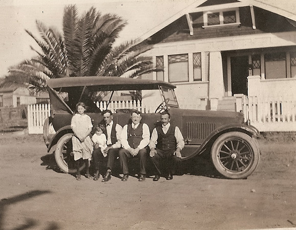In front of residence on Kettner blvd in 1925: L-R:  Edna Bregante, daughter Lillian Stagnaro on father Steve's knee, Gerolamo Bregante. Note unpaved Kettner blvd and sidewalk area.