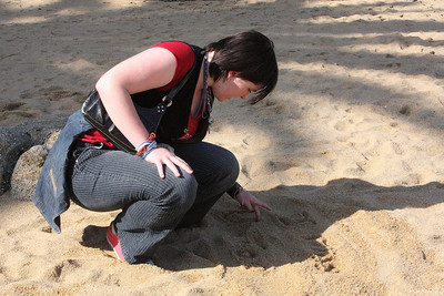 Tori writing a message to her friends in the sand at Monerey, CA