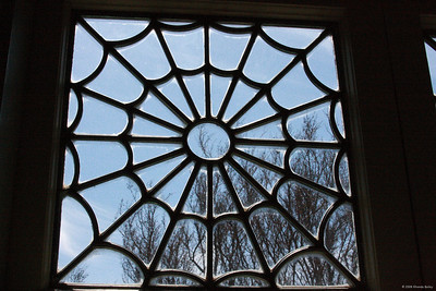 Leaded glass window in the Winchester Mystery House.  Mrs. Winchester liked spider webs and they can be found all over the house in windows and carved in wood.