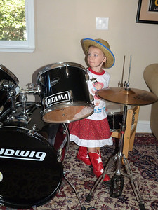 Playing the drums in their guest room.