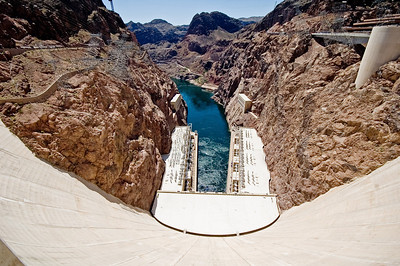 A wide shot of the dam looking down from the top with the power generators and colorado river valley below.