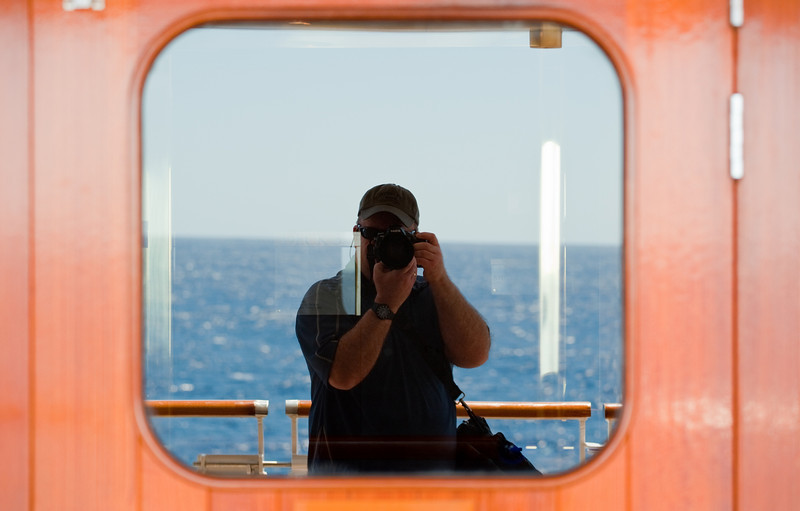 Mirrored self-portrait with ocean backdrop, taken in window of cruise ship.
