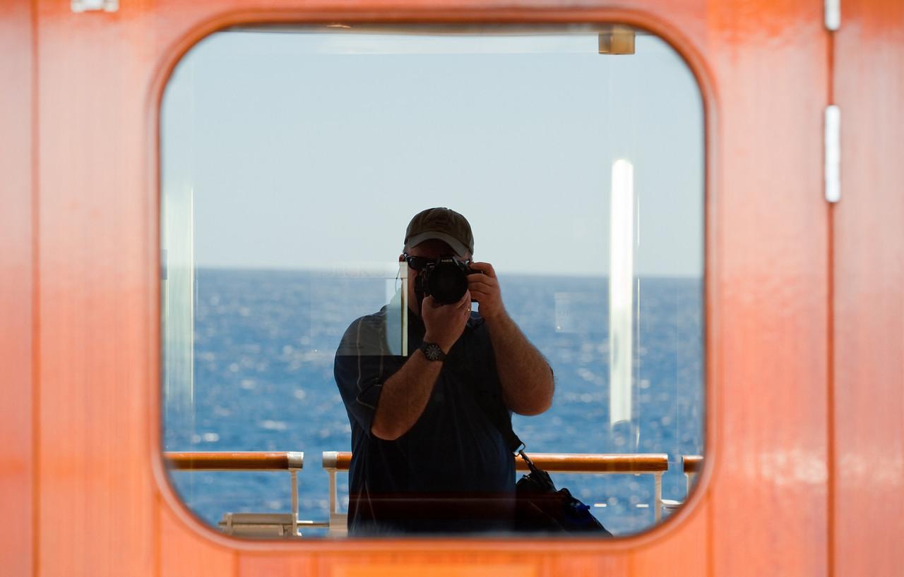 Mirrored self-portrait with ocean backdrop, taken in window of cruise ship.