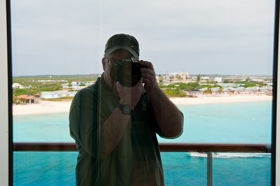 Self portrait taken using reflection from window, Grand Turk in the background.