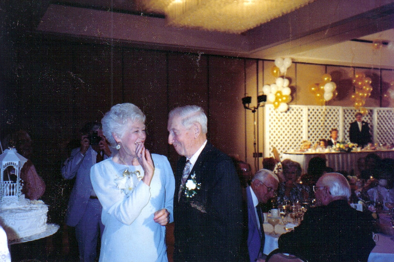 Mom and Dad sharing a laugh  at their 50th.  Mom just shoved the anniversary cake in Dad\'s mouth.