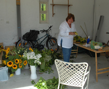 Sandra has turned the shed into her flower shop where she spends the entire day putting together bouquets.