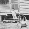 Parker on the steps of the Madre house, which the family lived in for a few years prior to moving to the Chappell house on the Center Hill Highway. This rental house was located off Ballahack Road near Hertford (behind the houses of brothers Will and Tom Madre). While we were living there Daddy ran over the rocking chair with his car. I cannot identify the woman in the porch behind me.<br /> <br /> JPC<br /> 2012.07.27